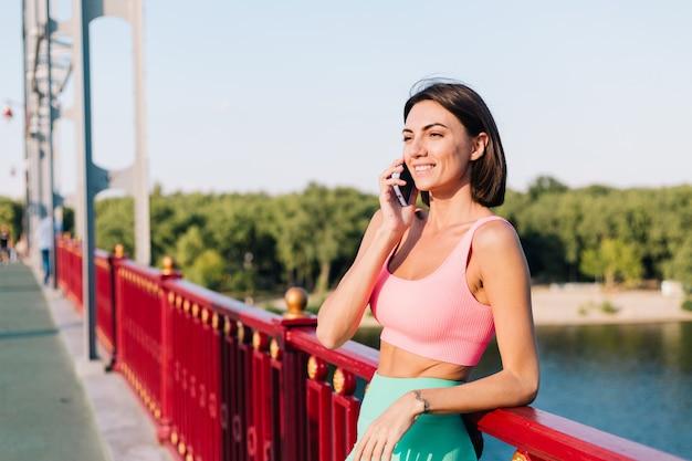 Sportieve vrouw in het passen van sportkleding bij zonsondergang bij moderne brug met uitzicht op de rivier, gelukkige positieve glimlach met mobiele telefoongesprekken die een gesprek voeren