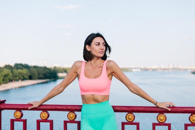 Sportieve vrouw in passende sportkleding bij zonsondergang bij moderne brug met uitzicht op de rivier, blije positieve glimlach Gratis Foto