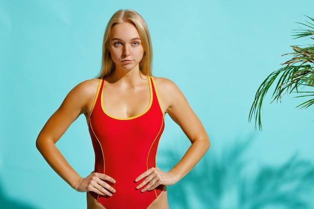 Sportieve vrouw in rode zwembroek vormt. meisje in badmode poseren