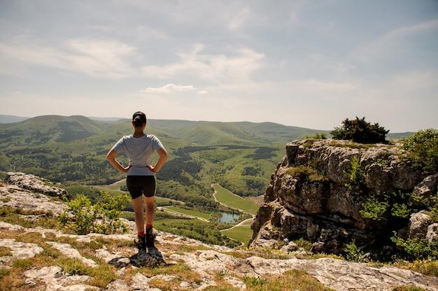 Sportieve vrouw in sportief uniform, sneakers en met een pet op haar hoofd staat op de bergtop