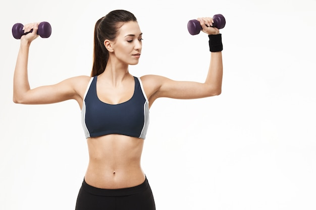 Sportieve vrouw in sportkleding opleidingswapens met domoren op wit.
