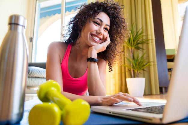 Sportieve vrouw in sportkleding zit op de vloer met halters met behulp van een pc-laptop in de woonkamer