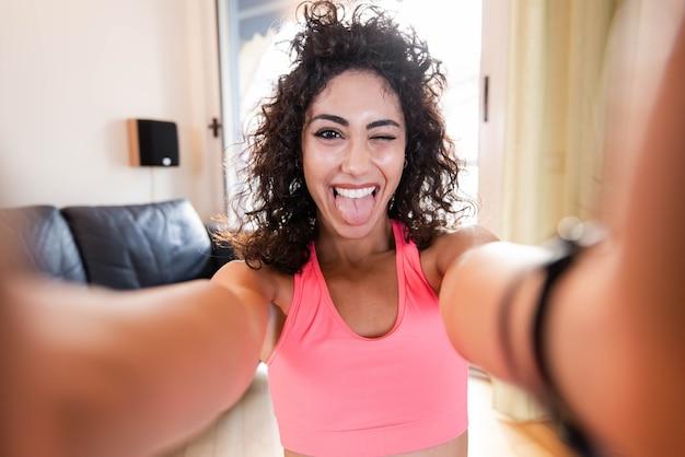 Sportieve vrouw in sportkleding zit op de vloer met halters met behulp van een selfie in de woonkamer