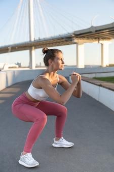 Sportieve vrouw in trendy sportkleding die buiten situp-oefeningen doet
