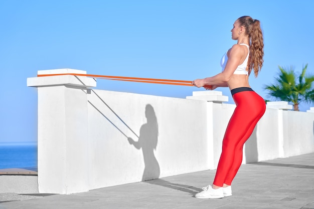 Sportieve vrouw in zomerochtend training op het strand in rode legging met rubberen weerstand band, atleet meisje training op zee kust achtergrond met fitness elastiek