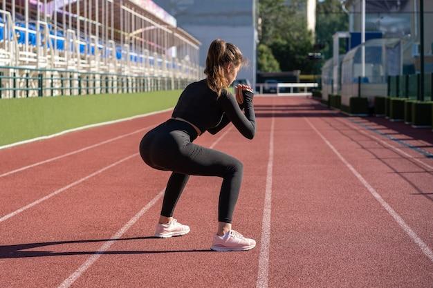 Sportieve vrouw in zwarte sportkleding gehurkt, cardiotraining maken