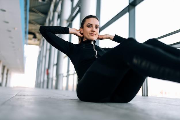 Sportieve vrouw in zwarte trainingspak die sit-ups binnen doen.