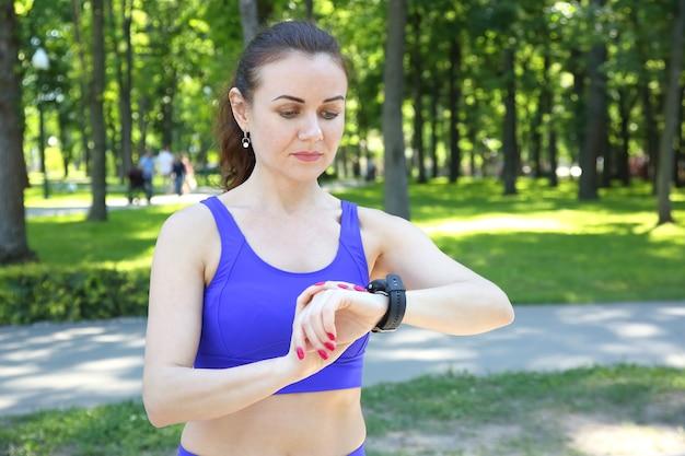 Sportieve vrouw kijkt naar de klok op zijn hand
