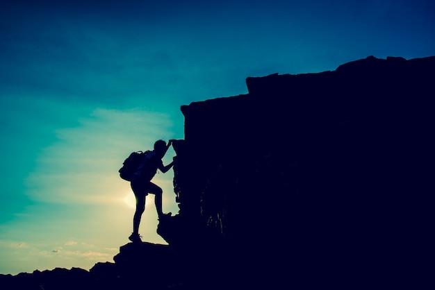 Sportieve vrouw klimmen op de klif. succes en doelconcept. sterk en gezond voor buitenactiviteiten. frisse start van de dag