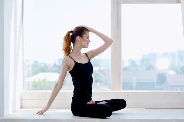 Sportieve vrouw mediteert in de buurt van venster yoga asana levensstijl