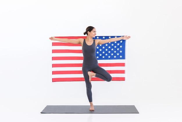 Sportieve vrouw met amerikaanse vlag die yoga beoefent op mat terwijl ze staan