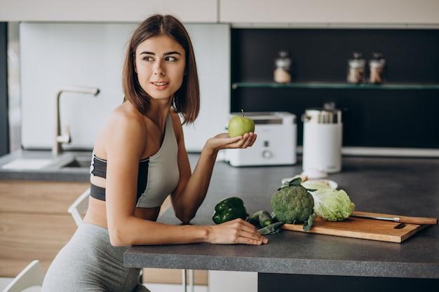 Sportieve vrouw met appel in de keuken