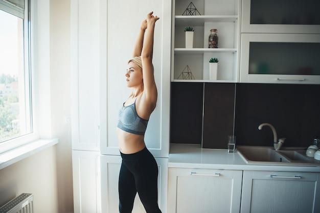 Sportieve vrouw met blond haar in sportkleding strekt zich uit in de keuken