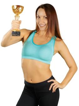 Sportieve vrouw met een gouden die trofeekop op wit wordt geïsoleerd