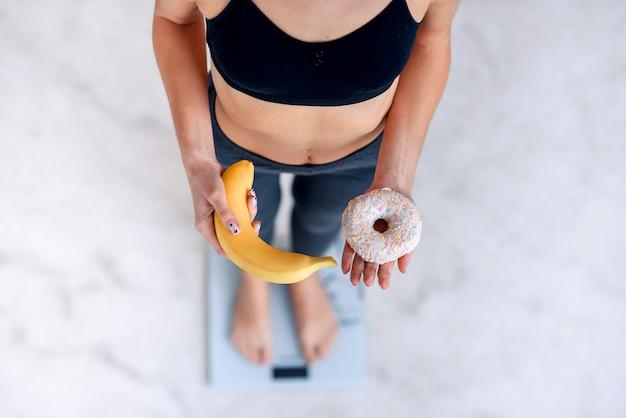 Sportieve vrouw met een perfect lichaam dat lichaamsgewicht op elektronische schalen meet en een doughnut en een gele banaan houdt