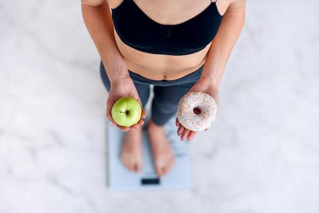 Sportieve vrouw met een perfect lichaam dat lichaamsgewicht op elektronische schalen meet en een doughnut en een groene appel houdt