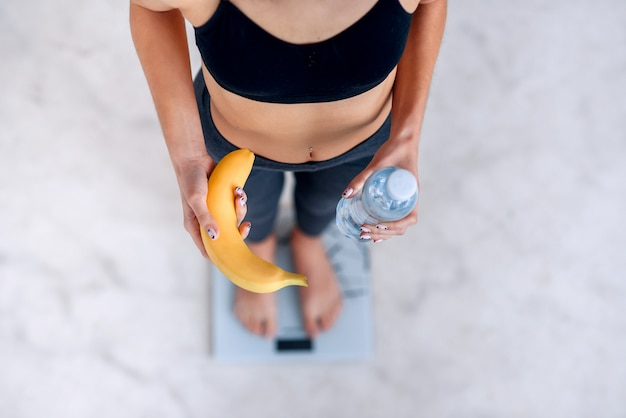 Sportieve vrouw met een perfect lichaam dat lichaamsgewicht op elektronische weegschalen meet en een gele banaan en een fles water vasthoudt