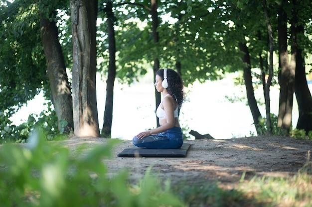 Sportieve vrouw met koptelefoon mediteren in de lotuspositie