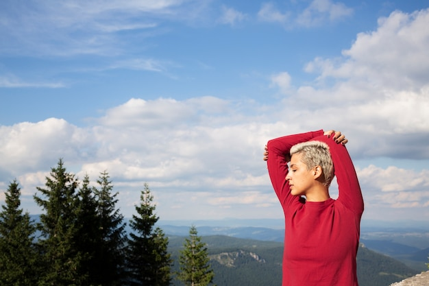 Sportieve vrouw met kort haar dat zich uitstrekt in de natuur