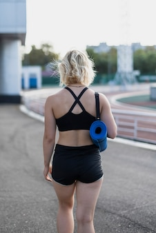 Sportieve vrouw met mat weggaan