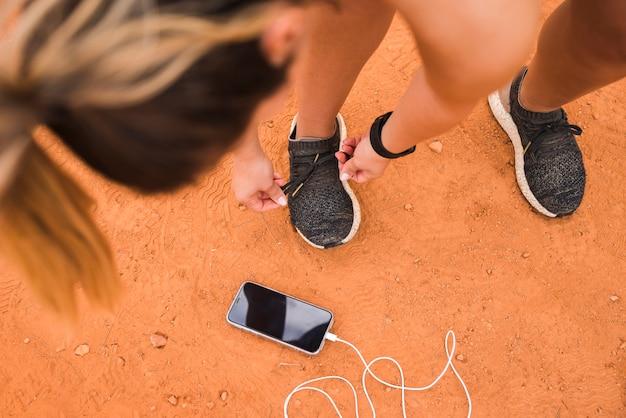 Sportieve vrouw met smartphone op stadionspoor