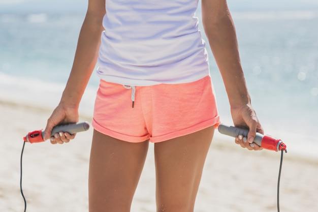 Sportieve vrouw met springtouw om te oefenen close-up