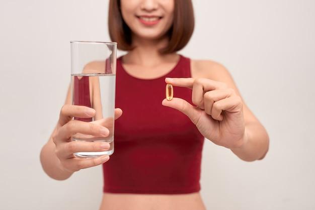 Sportieve vrouw met water en medicijnen op licht