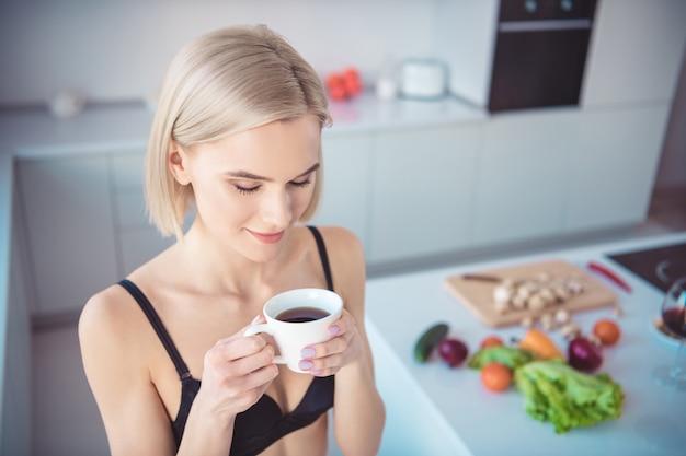 Sportieve vrouw poseren in de keuken in haar ondergoed