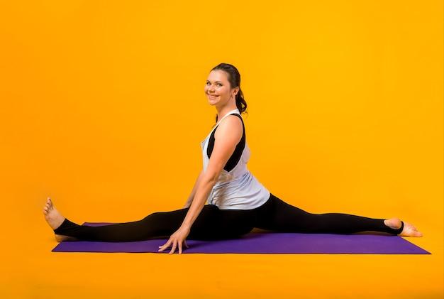 Sportieve vrouw spagaat op een paarse mat op een oranje muur