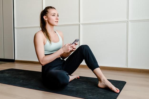 Sportieve vrouw thuis met telefoon op yoga mat