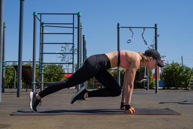 Sportieve vrouw trainen op het sportveld in zonnige zomerdag