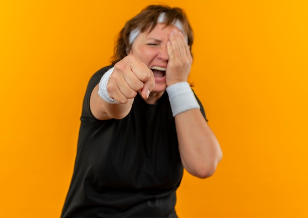 Sportieve vrouw van middelbare leeftijd in zwart t-shirt met hoofdband bang en boos wijzend met vuist naar camera die één oog bedekt met hand die over oranje muur staat