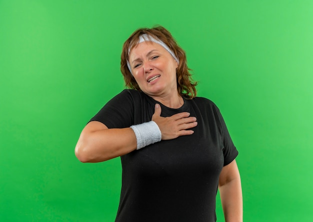 Sportieve vrouw van middelbare leeftijd in zwart t-shirt met hoofdband die hand op haar borst houdt die zich onwel bevindt zich over groene muur bevindt