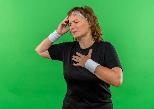 Sportieve vrouw van middelbare leeftijd in zwart t-shirt met hoofdband die onwel kijkt haar hoofd aanraken zich ziek en moe voelen staande over groene muur