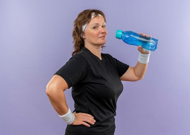 Sportieve vrouw van middelbare leeftijd in zwart t-shirt met hoofdband drinkwater na het werk die zich over blauwe muur bevinden