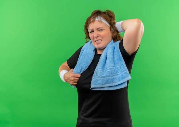 Sportieve vrouw van middelbare leeftijd in zwart t-shirt met hoofdband en handdoek op haar nek kijkt onwel aanrakende nek met pijn staande over groene muur