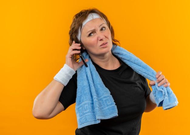 Sportieve vrouw van middelbare leeftijd in zwart t-shirt met hoofdband en handdoek op schouder op zoek moe praten op mobiele telefoon staande over oranje muur