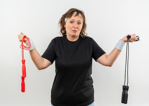 Sportieve vrouw van middelbare leeftijd in zwart t-shirt met hoofdband met twee springtouwen op zoek verward met twijfels staande over witte muur
