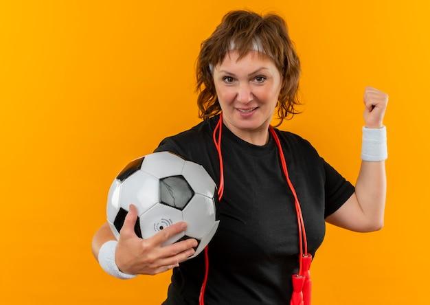 Sportieve vrouw van middelbare leeftijd in zwart t-shirt met hoofdband met voetbal houden vuist blij en positief, winnaar concept staande over oranje muur