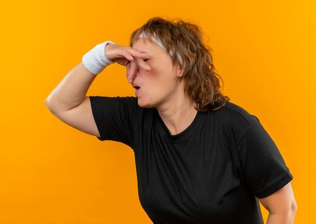 Sportieve vrouw van middelbare leeftijd in zwart t-shirt met hoofdband sluitende neus met vingers die aan stank lijden die zich over oranje muur bevindt