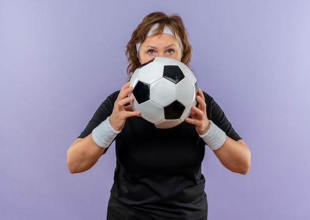 Sportieve vrouw van middelbare leeftijd in zwart t-shirt met voetbal die van de hoofdbandholding zelfverzekerd met ernstig gezicht over blauwe muur kijkt