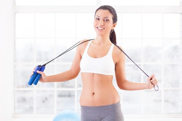 Sportieve vrouw. vrolijke jonge sportieve vrouw die een springtouw op haar schouders houdt en naar de camera kijkt terwijl ze in een sportclub staat