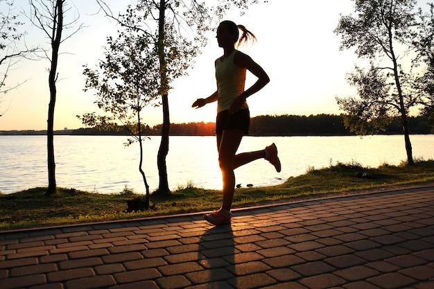Sportieve vrouwelijke jogger die buiten in de natuur rent en traint.