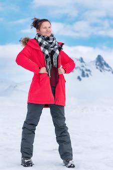 Sportieve vrouwelijke reiziger gekleed in een rood winddicht winterjack, zwart-witte sjaal om de nek, grijze sportbroek en wandelschoenen die bij koud winterweer in de bergen staan.
