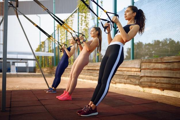 Sportieve vrouwen doen fitte oefening met touwen op sportveld, groepstraining buitenshuis