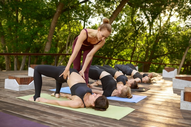 Sportieve vrouwen op groepsyoga-training met instructeur in zomerpark. meditatie, fitles tijdens training buitenshuis
