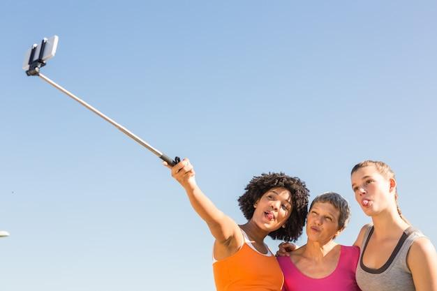 Sportieve vrouwen poseren en nemen selfies met selfiestick