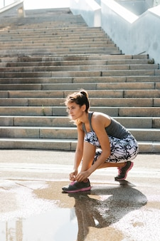 Sportieve vrouwen vastmakende schoenen in stedelijk milieu