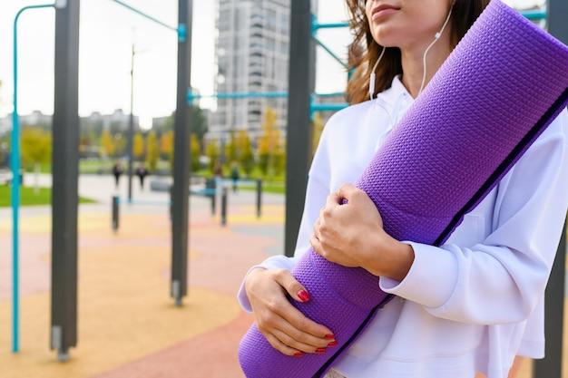 Sportieve vrouwenhanden houden opgerolde mat vast voor trainingsoefeningen op de achtergrond van het stadspark, gezond fit meisje geniet van buitenactiviteiten met muziek in een koptelefoon