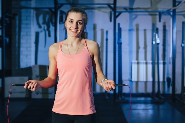 Sportieve vrouwentraining met touwtjespringen in crossfitgymnastiek